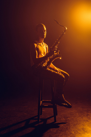 young jazzman looking at camera while sitting on stool and holding saxophone Stock Photo