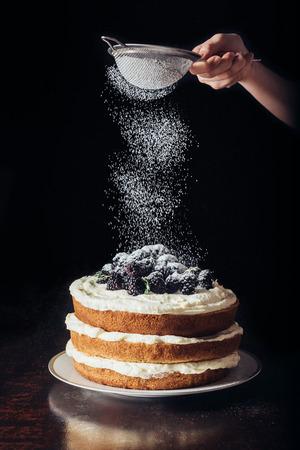 abgeschnittener Schuss der Frau, die Zuckerpulver auf köstliche Brombeere auf Schwarz verschüttet