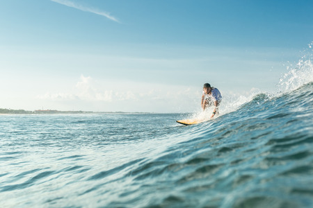 selective focus of male surfer riding on board in ocean at Nusa Dua Beach, Bali, Indonesia