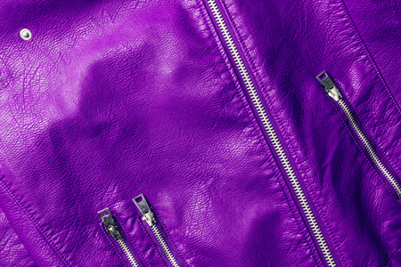 top view of violet leather shiny textile with zippers as background