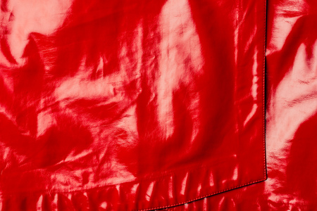 elevated view of red leather shiny textile as background