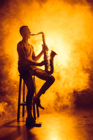 young professional musician sitting on stool and playing saxophone in smoke 스톡 콘텐츠