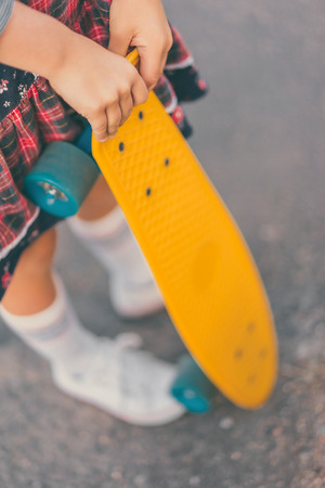 cropped image of little child standing with penny board at street