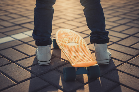 cropped image of little kid standing with skateboard at street Фото со стока