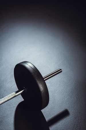 partial view of barbell on floor with shadow at gym Reklamní fotografie