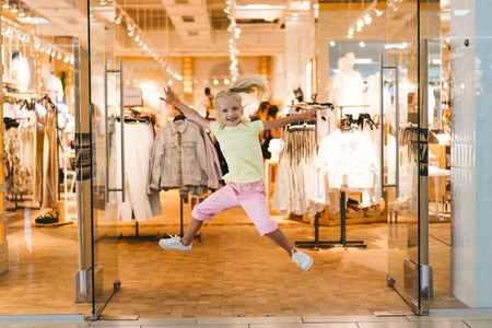 front view of excited little kid jumping with wide arms in shop