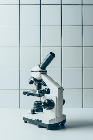 optical microscope on white tablet in front of tiled wall Zdjęcie Seryjne