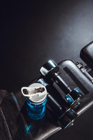 Draufsicht auf Sportflasche, Handtuch, Hanteln im Fitnessstudio, schwarzer Hintergrund