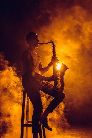 Jeune jazzman expressif assis sur un tabouret et jouant du saxophone