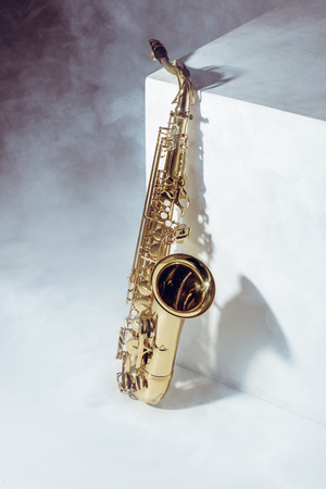 close-up view of professional saxophone in smoke on grey 스톡 콘텐츠