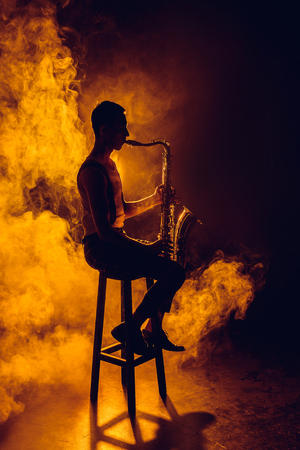 silhouette of young musician sitting on stool and playing saxophone in smoke
