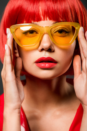 close-up portrait of beautiful young woman in vintage yellow sunglasses looking at camera