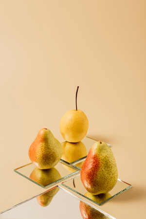 yellow whole pears reflecting in mirrors on beige table Фото со стока