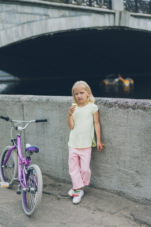 little child with ice cream standing near bicycle on street