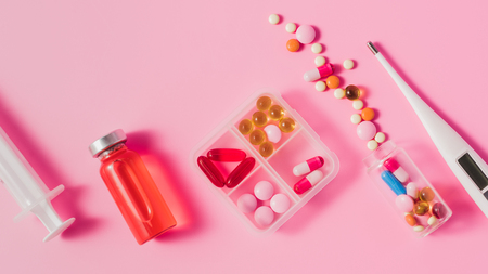 top view of different medicines and electric thermometer on pink surface Stock Photo