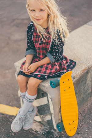 adorable smiling child sitting near skateboard and looking at camera at urban street Фото со стока