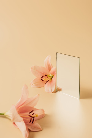 lily flowers and mirror on beige tabletop
