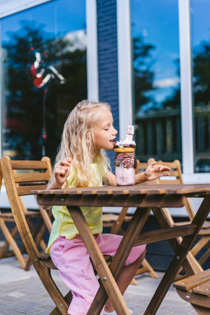selective focus of little child with closed eyes eating delicious dessert at table in cafe