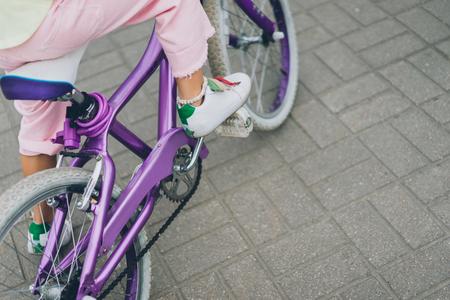 cropped shot of child riding bicycle on city street Фото со стока