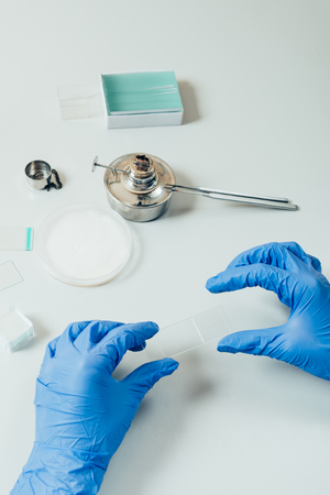 cropped image of scientist in latex gloves examining analysis in modern laboratory