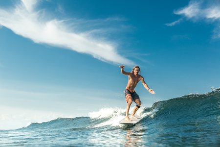 handsome shirtless male surfer riding waves in ocean at Nusa Dua Beach, Bali, Indonesia Banco de Imagens