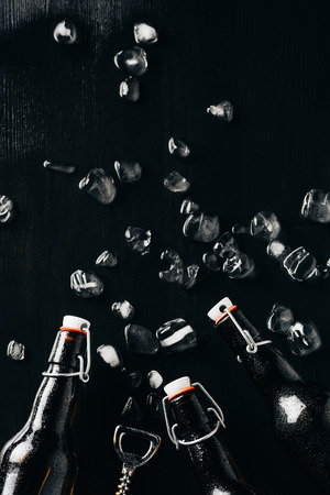 flat lay with bottle opener, glass bottles of beer and ice cubes arranged on dark tabletop