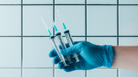 cropped shot of doctor in blue glove holding syringes in front of tiled white wall