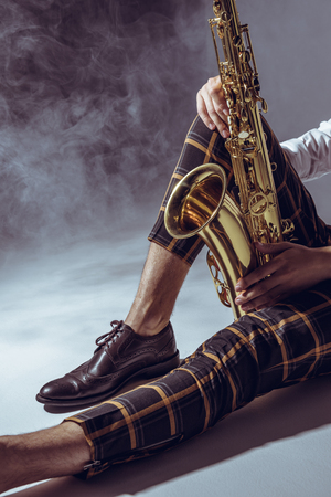 partial view of stylish young musician sitting with saxophone in smoke on grey