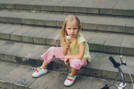cute child with ice cream sitting on city steps alone