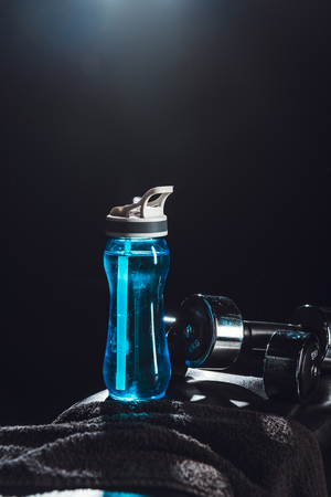close up view of sport bottle, towel, dumbbells at gym, black background