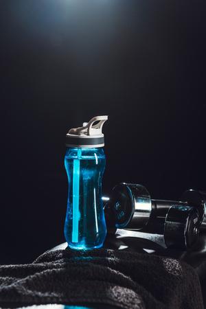 Nahaufnahme der Sportflasche, des Handtuchs, der Hanteln im Fitnessstudio, schwarzer Hintergrund