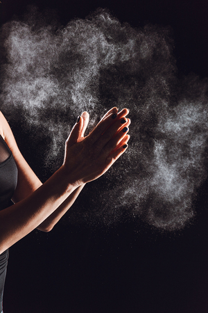 cropped image of sportswoman spreading chalk powder in hands, black background
