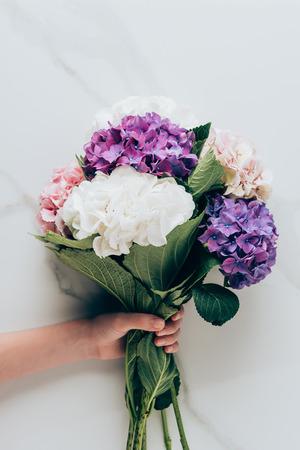 vue recadrée de femme tenant un bouquet de fleurs d'hortensia sur la surface en marbre