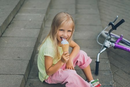 cute child with ice cream sitting on city steps near bicycle alone