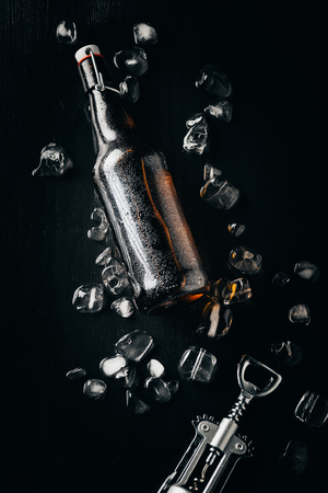 flat lay with bottle opener, bottle of beer on ice cubes arranged on dark tabletop Stock Photo - 106421276