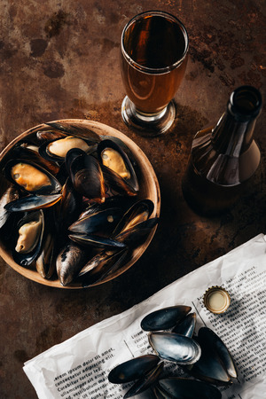 top view of arranged glass and bottle of beer, newspaper and mussels in bowl on rust surface