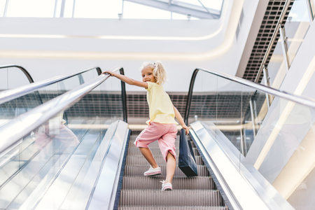 low angle view of smiling little child with shopping bag in hand on escalator at mall