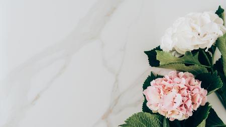 Draufsicht von rosa und weißen Hortensienblumen auf Marmoroberfläche mit Kopienraum Standard-Bild