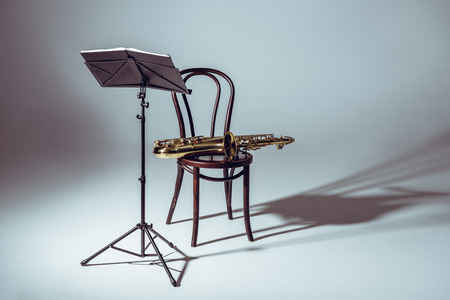 music stand for notes and saxophone on chair in studio