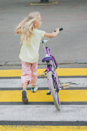 back view of little kid with bicycle crossing road Reklamní fotografie