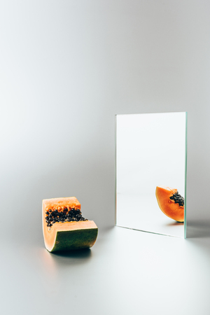one piece of papaya reflecting in mirror on white table