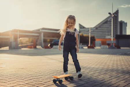 smiling adorable child standing with skateboard at parking lot