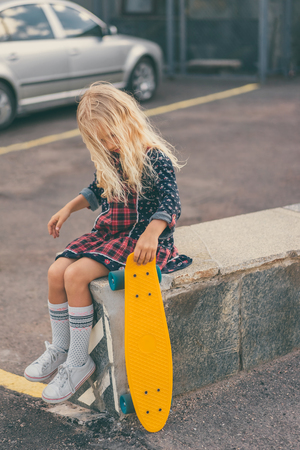 adorable kid holding skateboard and sitting at urban street 版權商用圖片 - 106421537