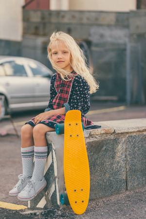 adorable child sitting near skateboard and looking at camera at urban street Фото со стока
