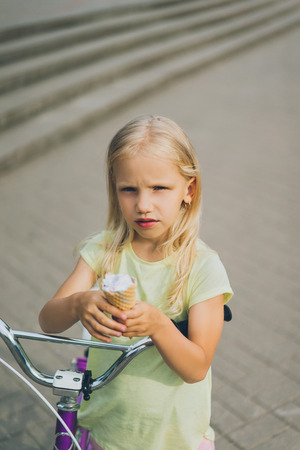 portrait of adorable little kid with ice cream and bicycle standing on city street Imagens