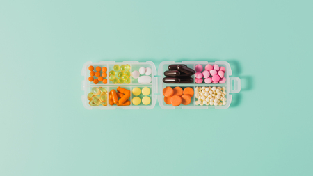 top view of plastic case with various sorted pills on blue