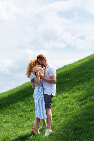 young redhead woman covering face by straw hat while kissing with boyfriend on green hill