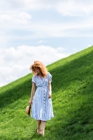 redhead woman posing with straw hat on grassy hill against blue sky Stock Photo