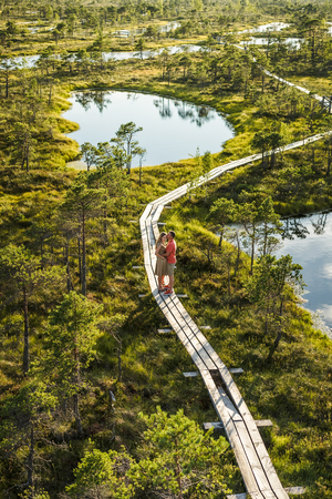 aerial view of couple in love on wooden bridge with green plants on background Foto de archivo - 106421718