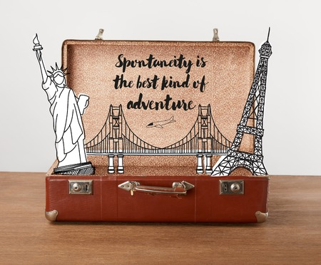 Open vintage travel bag with illustration and lettering - Spontaneity is the best kind of adventure Stock Photo